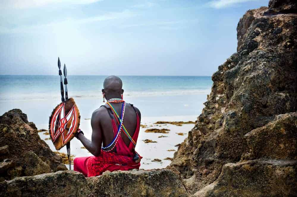 Kenyan warrior sitting on the beach
