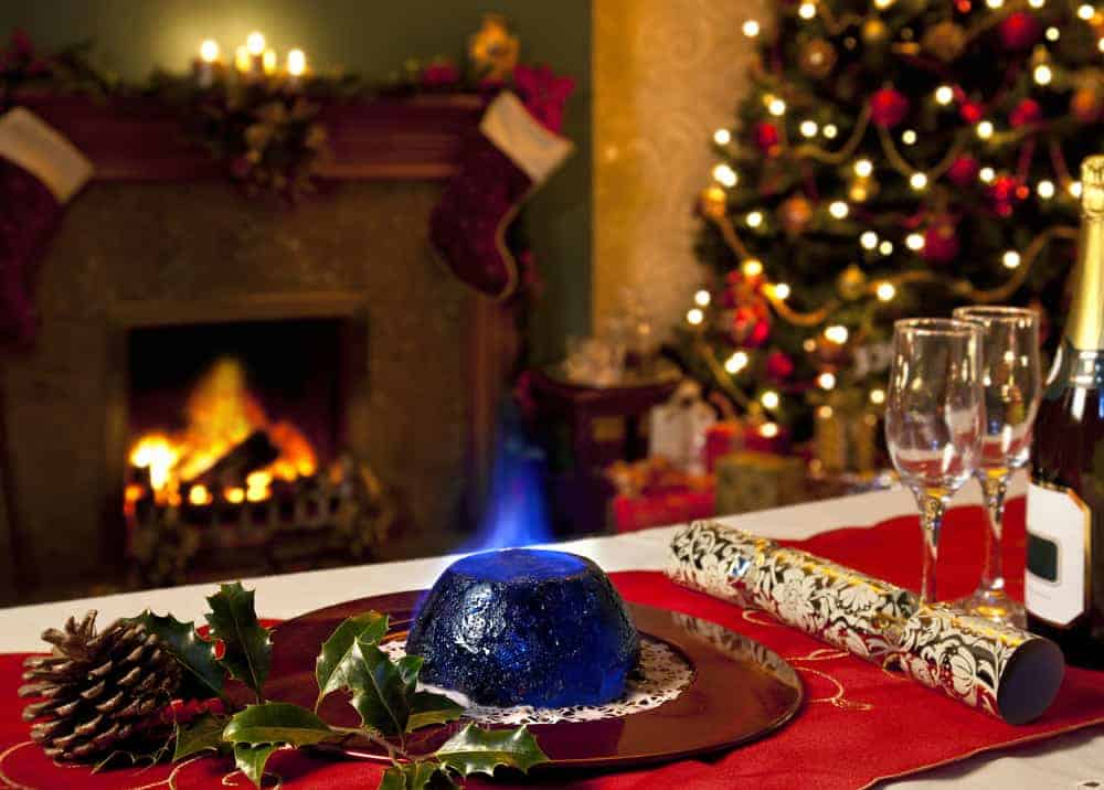 A Christmas Pudding with burning brandy topping with a festive background of fireplace and Christmas tree.