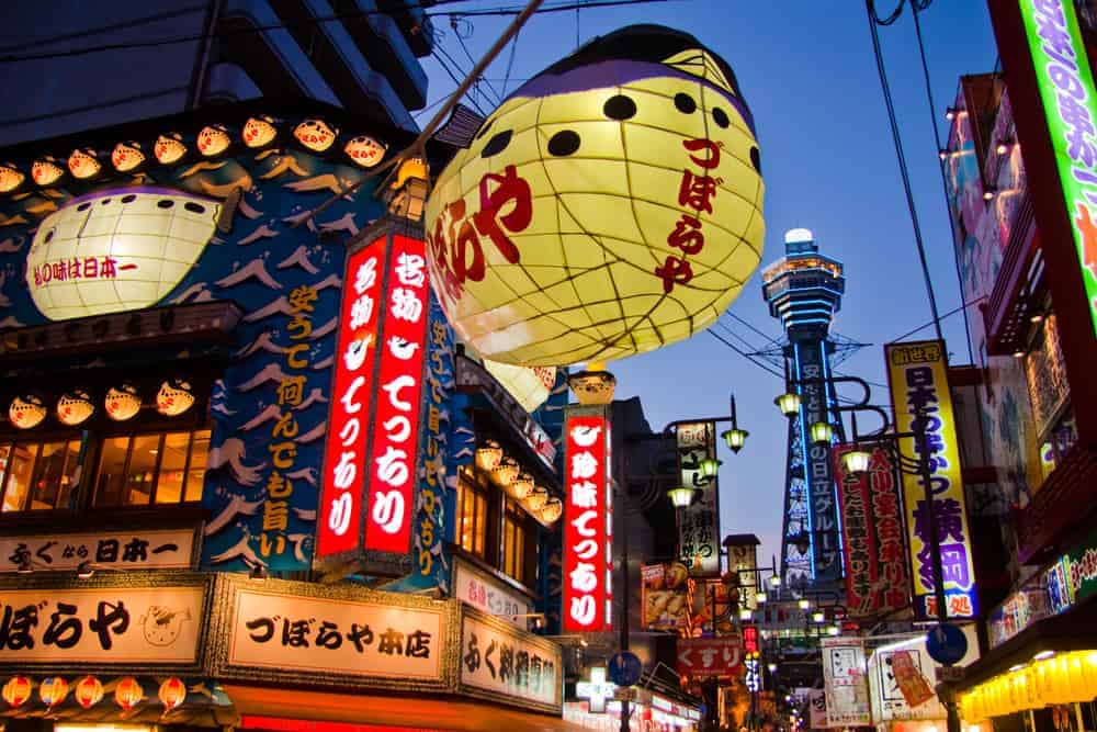 The Tsutenkaku Tower visible above the neon of Osaka's night scene.