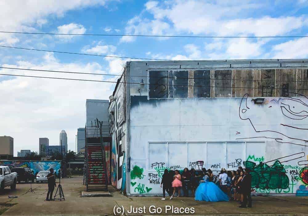 A photo shoot with a quinceanera in a blue dress at the Houston Graffiti building with a view of the skyscrapers of Downtown Houston