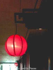 The hallway lights are reminiscent of red Chinese lanterns.