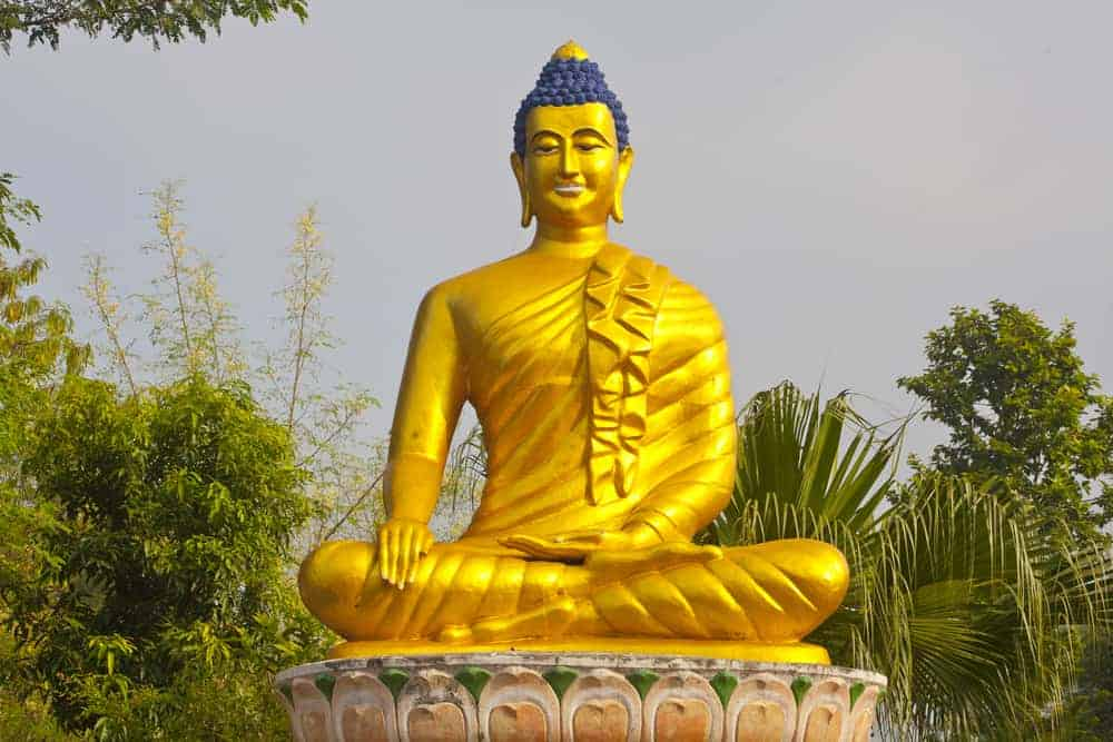 A statue of Buddha in one of the sacred places of Buddhism in Lumbini, Nepal where the Buddha was born.