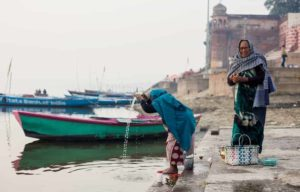 Praying on the banks of the Ganges River, a Hinduism holy place, in the city of Varanasi in India.