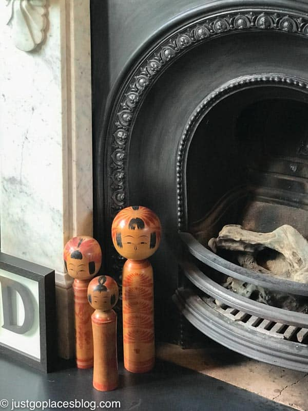 A collection of vintage Kokeshi dolls by a fireplace in a London Victorian home.