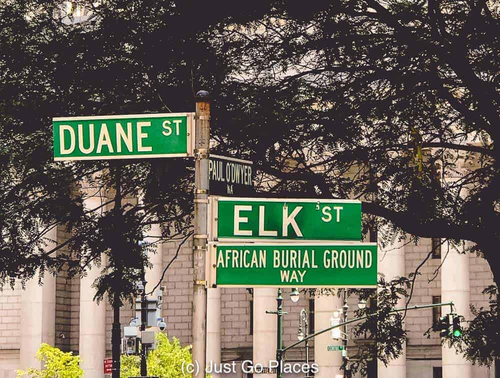 A street sign showing the way to the African Burial Ground NY