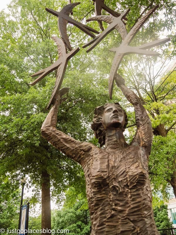 public sculpture of woman and birds