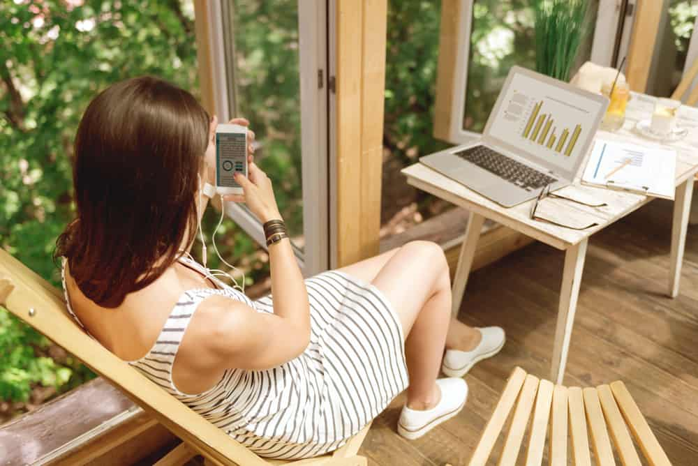 woman using phone with computer