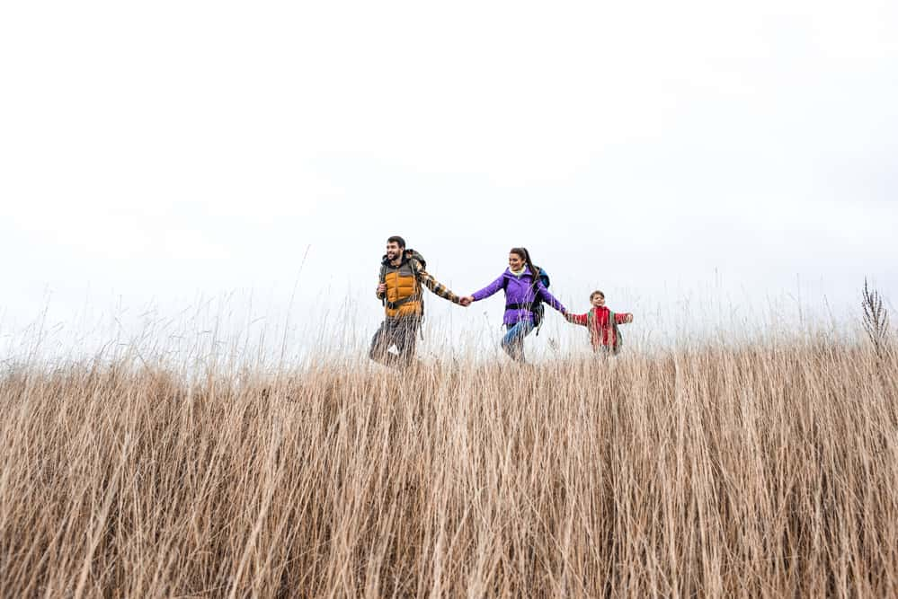 family backpacking through grass