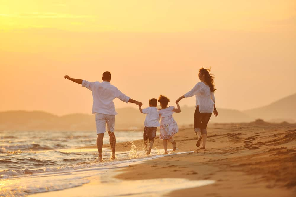 family on beach at sunset