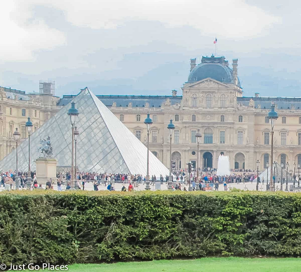 the famous glass pyramid in front of the Louvre Museum and people milling