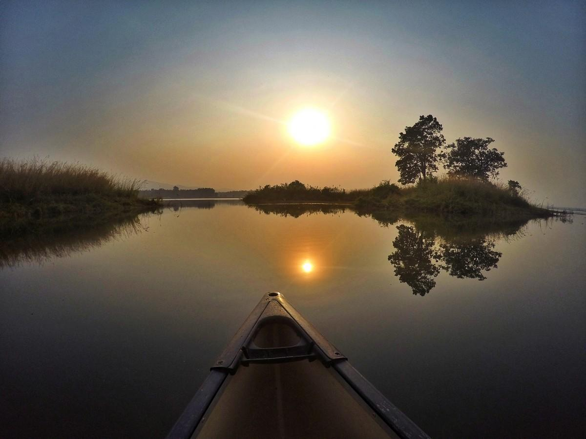 the tip of a canoe on the river at sunset