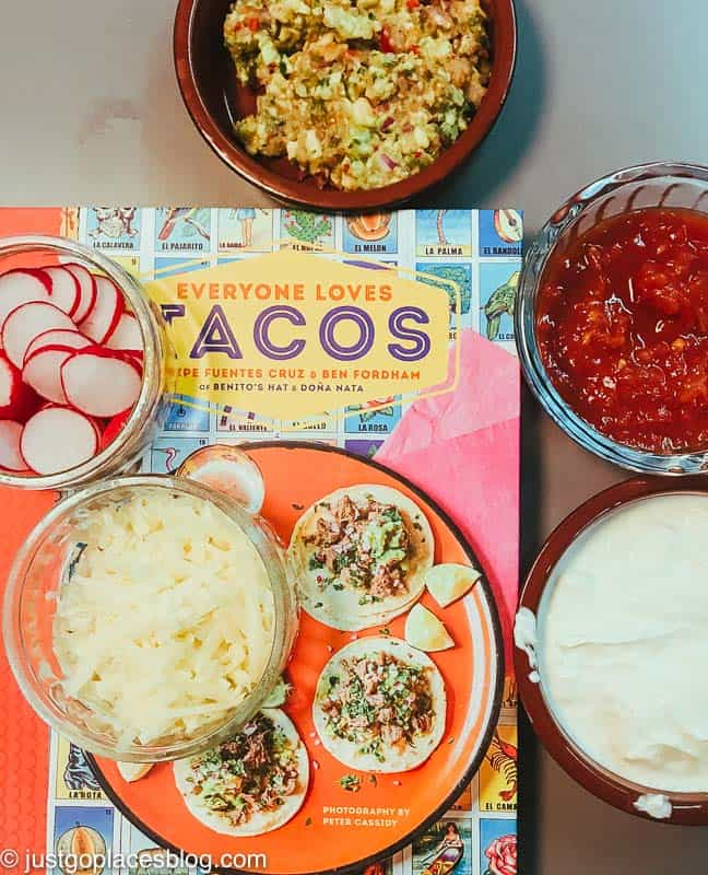 The cookbook named Everyone Loves Tacos with an assortment of Taco sides