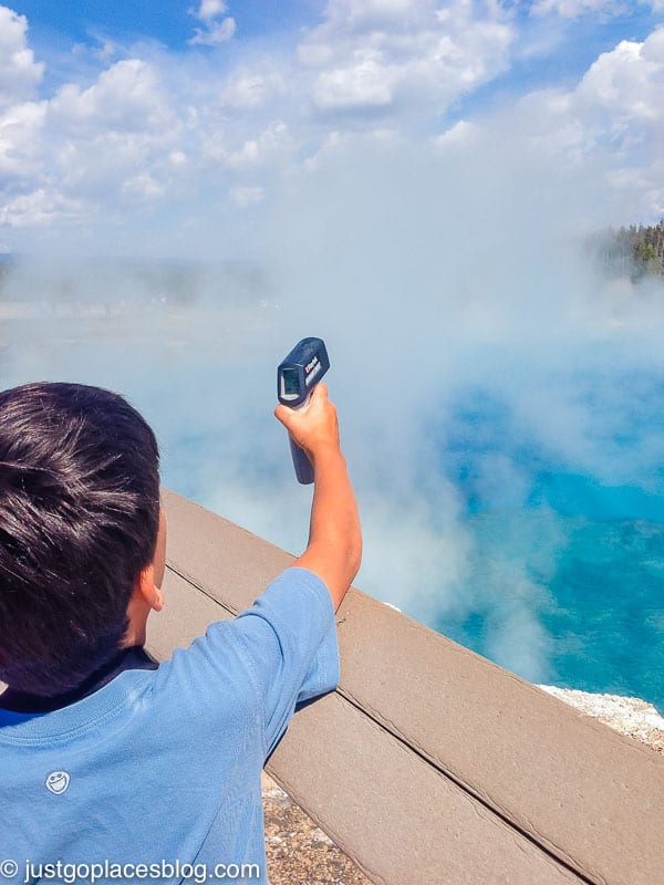 boy using a temperature gauge at the Grand Prismatic Spring