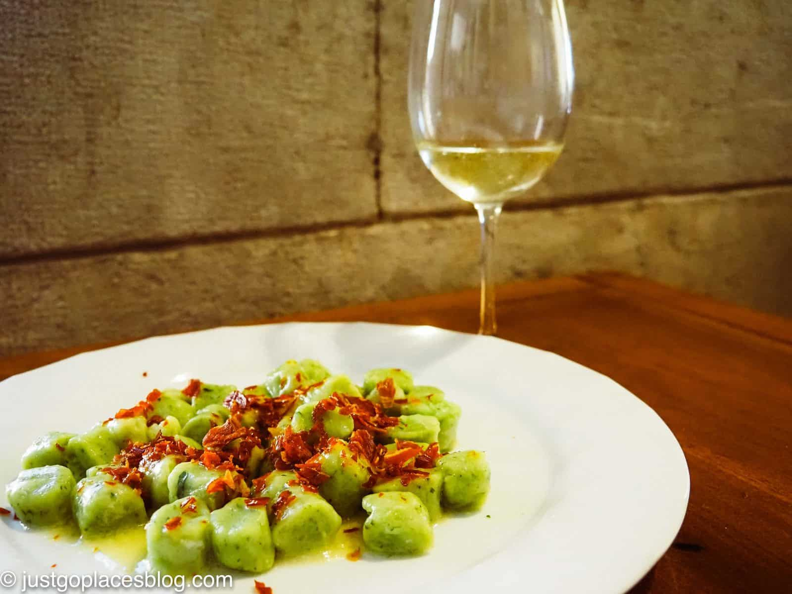 a plate of gnochetti with San Daniele ham and a glass of white wine