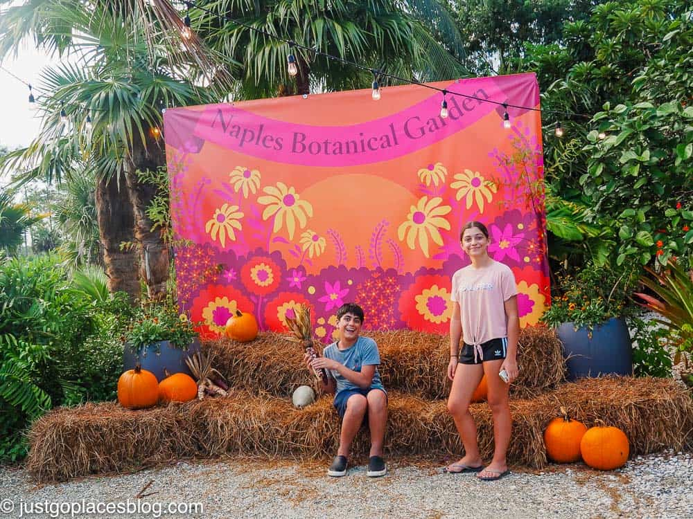 kids posing with pumpkins at Fall Walk Naples Botanical Gardens