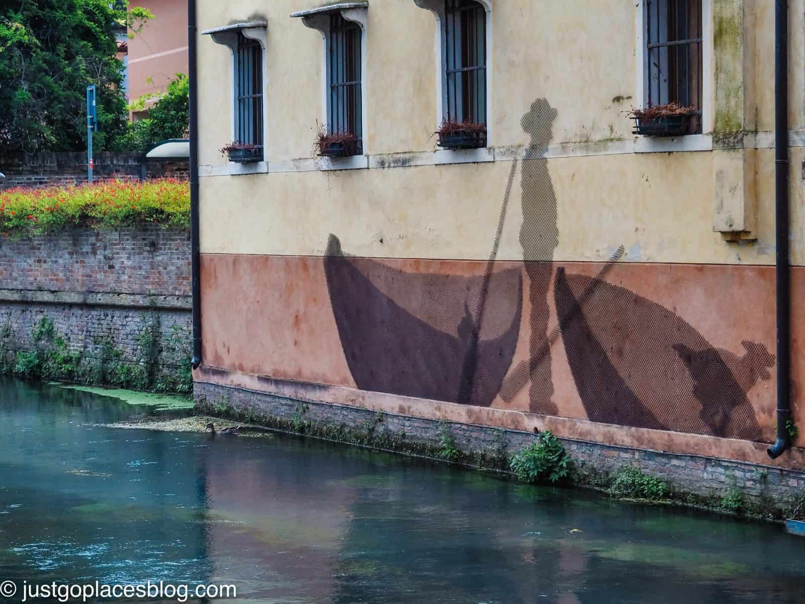 Street art of fisherman and nets canalised in Treviso
