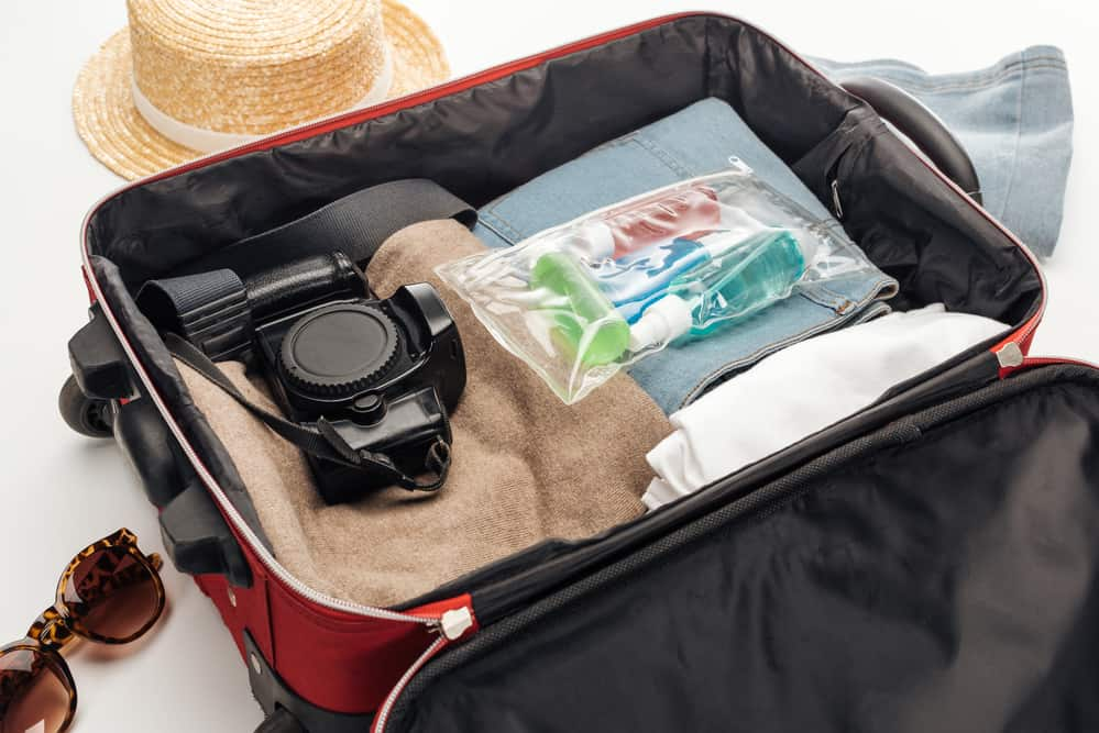 a suitcase packed with clothes, toiletries an a camera