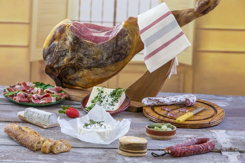 Jamon serrano. Traditional Spanish ham on black close up. Dry cured spanish pork ham in a plate.old vintage wooden background