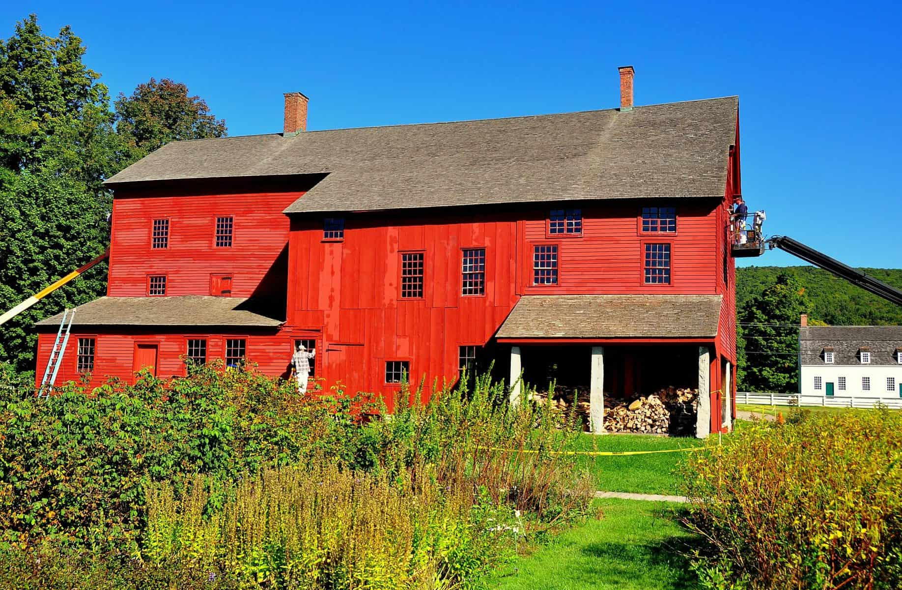 Workers on cherry pickers and ladders painting the large red 1790 Laundry and Machine shop  at the Hancock Shaker Village