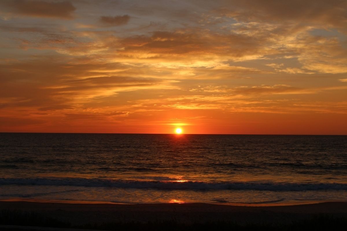 a sunrise over the beach in Outer Banks