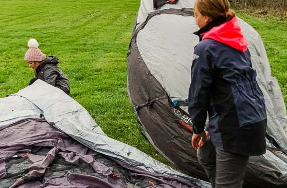 adjusting the tarp underlay while setting up a tent for camping