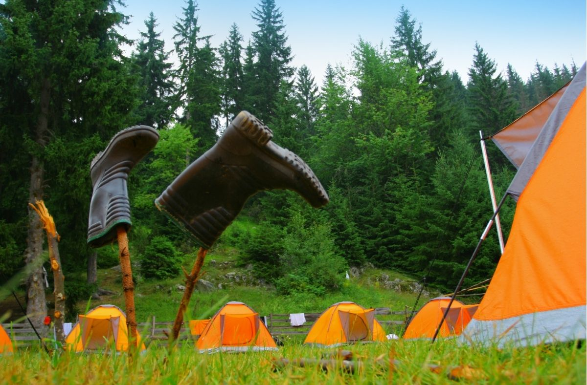 wellington boots drying on sticks near a campsite with orange tents