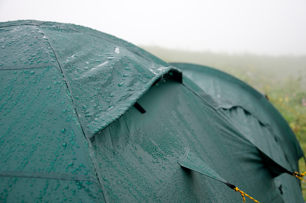 rain drops falling on a green tent while camping