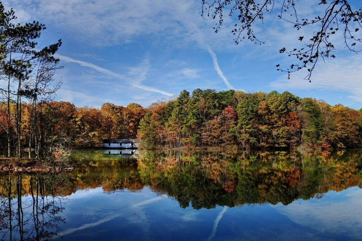 Fall foliage trees and blue sky reflected in a blue pond at Madison County Nature Trail