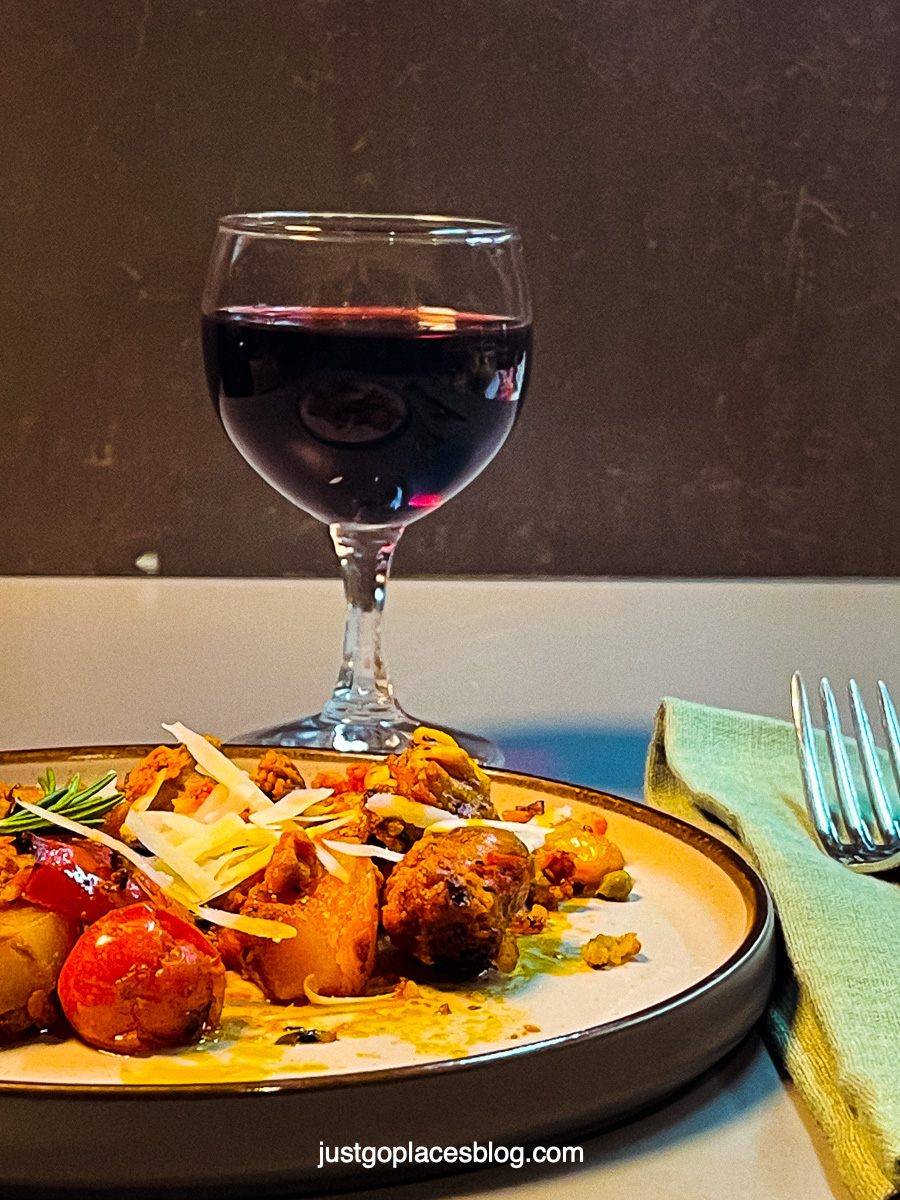 Italian sausage and potato dish with a glass of red wine